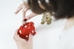 Kobiety oszczędzania pieniądze z czerwonym prosiątko bankiem fotografia stock