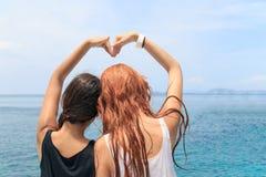 Kobiety para tworzy kierowego kształt z rękami przy morzem Fotografia Stock