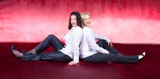 Kobiety pary siedzący plecy przeciw plecy i target221_0_ Zdjęcie Stock