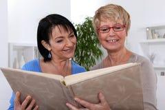 Kobiety patrzeje przez albumu fotograficznego Obraz Royalty Free