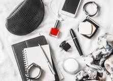 Kobiety piękna akcesoria na lekkim tle, odgórny widok Kosmetyczna torba, czerwony gwoździa połysk, tusz do rzęs, zegarek, bransol fotografia stock