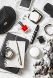 Kobiety piękna akcesoria na lekkim tle, odgórny widok Kosmetyczna torba, czerwony gwoździa połysk, tusz do rzęs, zegarek, bransol zdjęcie stock