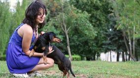 Kobiety piękny młody szczęśliwy z długim ciemnym włosy w błękit sukni trzyma małego jamnika psa zbiory wideo