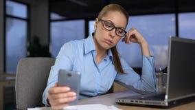 Kobiety pisać na maszynie wiadomość na telefonie komórkowym zamiast pracować, zanudzam przy niepopularną pracą zbiory