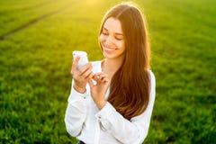 Kobiety pisać na maszynie wiadomość w telefonie w greenfield obraz stock