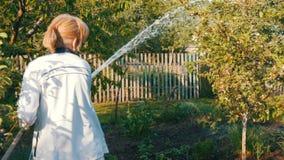 Kobiety podlewanie od węża elastycznego roślina w jej swój ogród zbiory