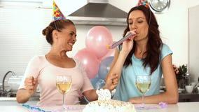 Kobiety podmuchowa świeczka podczas gdy świętujący jej urodziny z przyjacielem zbiory