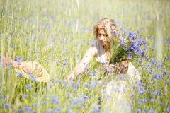 Kobiety podnosi błękitów kwiaty Zdjęcie Royalty Free