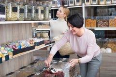 Kobiety podnosi dokrętki i wysuszone owoc w sklepie Zdjęcie Royalty Free