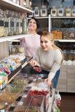 Kobiety podnosi dokrętki i wysuszone owoc w sklepie Obrazy Royalty Free