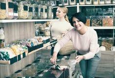 Kobiety podnosi dokrętki i wysuszone owoc w sklepie Zdjęcia Stock