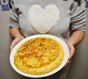 kobiety pokazuje na bielu talerzu hiszpańskiego omlet gotującego z jajkami i grulami Kobieta jest ubranym koszula z dużym białym  zdjęcia stock