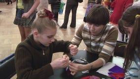 Kobiety pomaga dziewczyna z kwiatem na głowie robi miękkim ręcznie robiony lalom przy stołem festiwale Krawat nić zbiory wideo