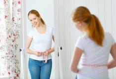 Kobiety pomiarowa talia przed lustrem Zdjęcia Stock