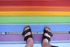 Kobiety pozycja na ławce malującej w tęczy barwi obraz stock