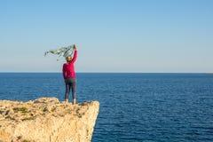 Kobiety pozycja na skalistym brzeg z szalikiem trzepocze w wiatrze, Obrazy Royalty Free