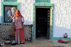Kobiety pozycja przed domem przy Jaisalmer, Rajasthan pustynia Zdjęcia Stock