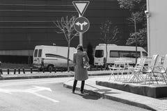 Kobiety pozycja przed drogowym znakiem i zastanawiać się gdzie iść obraz royalty free