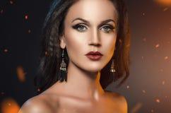 Kobiety pozycja w iskrach ogień Fasonuje portret brunetka w czarnych kolczykach na ciemnym tle obrazy royalty free