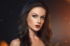 Kobiety pozycja w iskrach ogień Piękno portret brunetka w czarnych kolczykach na ciemnym tle Zdjęcie Royalty Free