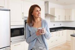 Kobiety pozycja W Nowy luksus Dostosowywającej kuchni Zdjęcie Stock