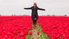 Kobiety pozycja w polu tulipany obrazy stock