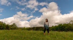 Kobiety pozycja w zieleni polu z chmurami za zdjęcia royalty free