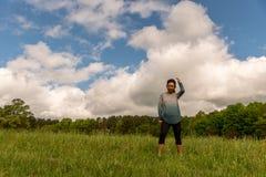 Kobiety pozycja w zieleni polu z chmurami za zdjęcie stock
