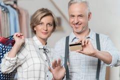 Kobiety pozycja z torba na zakupy i mężczyzna pokazuje kredytową kartę Zdjęcia Stock