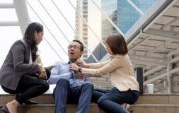 Kobiety próbują pomagać jej przyjaciela ma surowego klatka piersiowa ból jako atak serca w miasta tle Zdjęcia Royalty Free