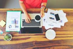 Kobiety pracuje trzyma filiżanka kawy freelancer używać laptop i rękę w ministerstwo spraw wewnętrznych, technologia komunikacyjn obraz royalty free