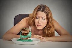 Kobiety pragnienia cukrowi słodcy ciastka ale martwiący się o ciężaru zysku obraz royalty free