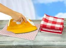 Kobiety prasowania tablecloths na wieśniaku siwieją stół z błękitnym bielem fotografia royalty free