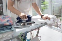 Kobiety prasowanie Odziewa Używać żelazo Na prasowanie desce zdjęcie royalty free
