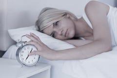 Kobiety przedłużyć ręka budzik w łóżku Obrazy Royalty Free
