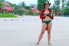 Kobiety przedstawienia czerwony szynel i bikini na plaży zdjęcie stock