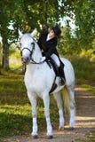 Kobiety przejażdżka na białym koniu w drewnie Zdjęcia Stock