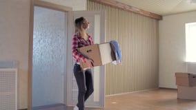 Kobiety przewożenia karton inside w ich nowym domu zbiory