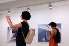 Kobiety przy fotografii exhition używać smartphones, urządzenia przenośne i ogólnospołecznego sieć nałóg, zdjęcie royalty free