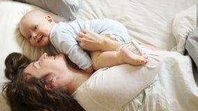 Kobiety przytulenie i ?askotanie jej roczniaka syn Pogodna rodzinna ranek mama, dziecko w ? zbiory