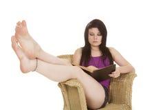 Kobiety purpura w krześle czytającym iść na piechotę up obraz stock