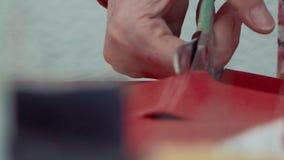 Kobiety ręki nożyce cią nożyce czerwoną tkaninę na patroszonej linii zbiory