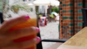 Kobiety ręka bierze szkło piwo i stawia je na stole Uliczna kawiarnia w Europejskim mieście zbiory wideo