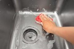 Kobiety ręka czyści kuchennego zlew Obrazy Royalty Free