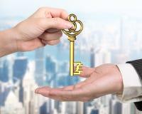 Kobiety ręka daje funta znaka skarbu kluczowi mężczyzna ręka Zdjęcia Stock