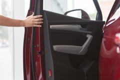 Kobiety ręka dalej otwiera nowego czerwonego samochodowego drzwi tło obraz stock