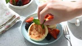Kobiety ręka dekoruje śniadaniowych bliny z nowym liściem zdjęcie wideo