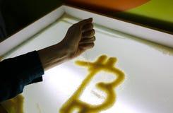 Kobiety ręka jest rysunkowym bitcoin z piaskiem na szkło zaświecającej powierzchni Pieniężny wzrostowy cryptocurrency Sztuka i bi zdjęcia stock