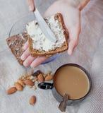 Kobiety ręka naciera masło na kawałku chleb Zdjęcia Stock