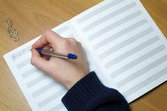 Kobiety ręka napisał na papierowych notatkach, treble zdjęcie royalty free